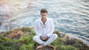 Tom Cronin crossed legged meditating on the side of a cliff with the ocean behind him
